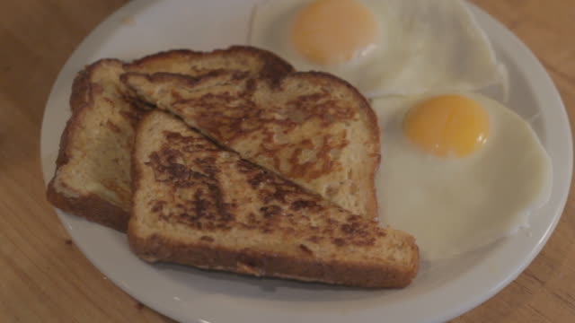 Person drizzling syrup on french toast with over easy eggs on the plate from raised side view.