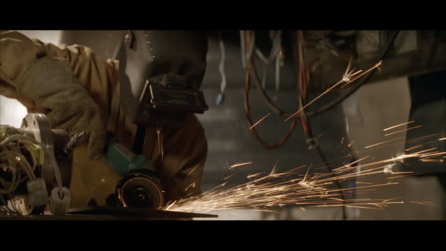 MS Person grinding metal and sparks  coming from grinder / Unspecified