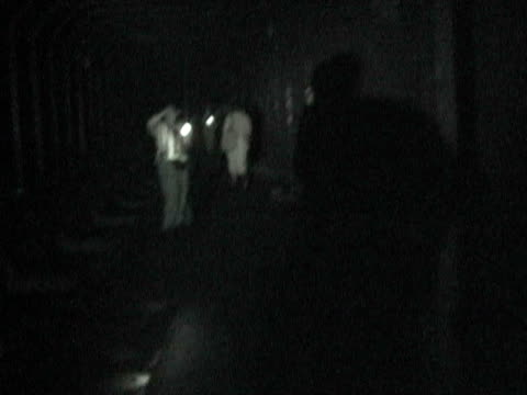 Person holding flashlight in subway tunnel as people walk past during citywide blackout on August 14 2003 / New York New York USA / AUDIO