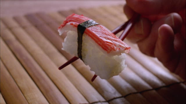 CU, Person holding sushi with crab stick, close-up of hand