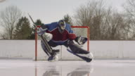 SM WS Person in foreground shooting hockey puck at goal/ Goalie stopping puck with leg/ Long Island, NY