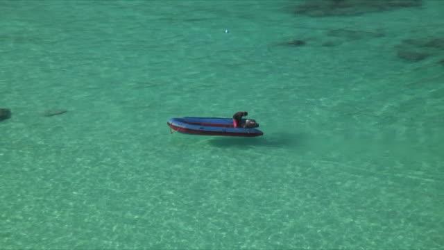 CU ZO HA WS Person in inflatable pontoon boat heading toward beach, Similan Islands, Thailand