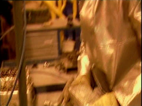 Person in protective silver suit moves blocks of gold at Pascua-Lama gold mine Chile; 29 Dec 06