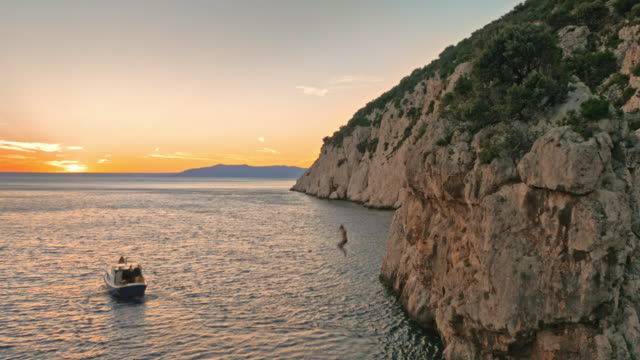 AERIAL Person jumping off cliff into sea at sunset