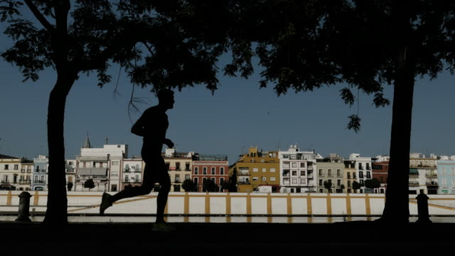 Person making exercise silouhete with triana neibourhood in seville in background