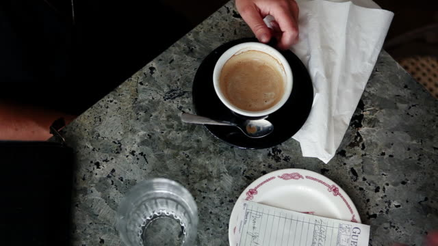 Person paying check in coffee bar