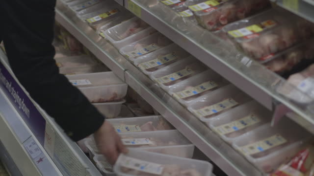 A person picks up a packet of chicken thighs at a large UK supermarket.