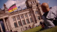 A person relaxing outside the Reichstag followed by a closeup of the German flag