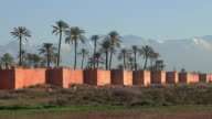 WS Person riding motorcycle along city walls with Atlas Mountains in background / Marrakech, Morocco