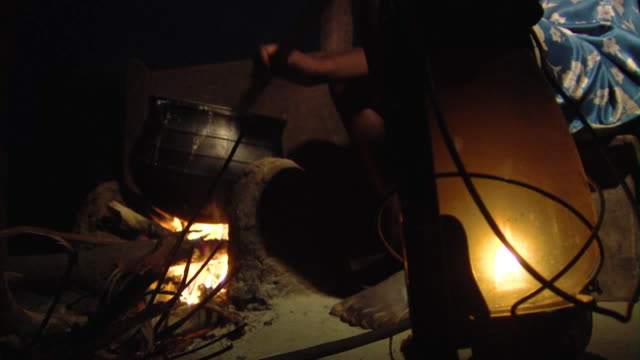 MS Person stirring food in pot on open fire at night, Tamale, Ghana