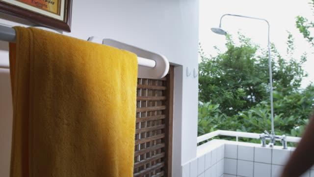 SLO MO MS Person taking yellow towel off towel rack in outdoor shower, Arnos Vale, Tobago, Trinidad And Tobago