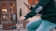 SLO MO Person typing sms on the bicycle