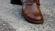 Person walking along crushing a cigarette butt with shoe