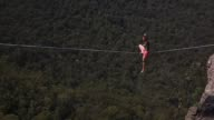 A person walks on a highline rigged between cliffs at Corroboree Walls in Mount Victoria on March 6 2015 in the Blue Mountains Australia On March...