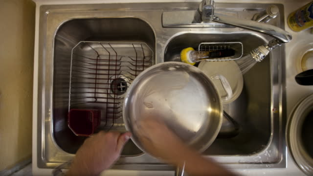 T/L MS HA Person washing stack of dirty dishes in kitchen sink / New York City, New York State, USA