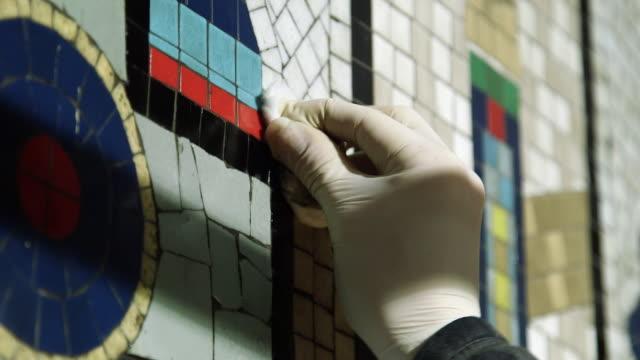 CU TU TD TS Person working on mosaic renovation at Tottenham Court Road Underground Station / London, England, United Kingdom