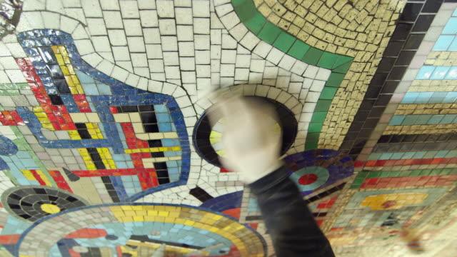CU HA Person working on mosaic renovation at Tottenham Court Road Underground Station / London, England, United Kingdom
