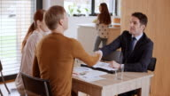 Personal banker visiting couple and shaking hands when meeting ends