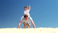 Personal trainer  - father and son do press ups on the beach