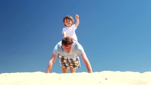 Persönliche trainer-Vater und Sohn machen Presse ups am Strand
