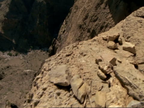 POV of person/animal walking along rocky cliff edge, Oman
