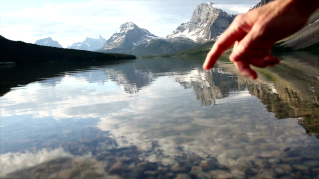 Person's finger touches surface of mountain lake