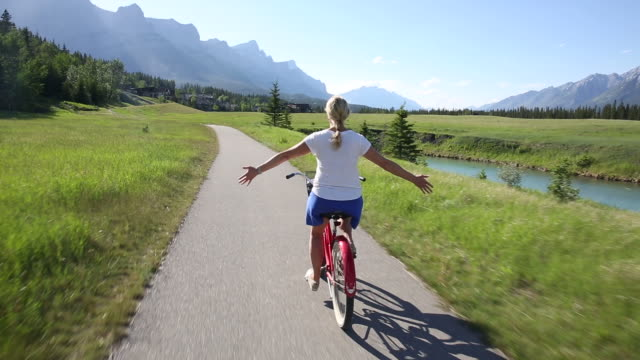 POV perspective of woman riding cruiser bicycle on paved path