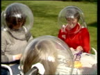 Perspex helmet invention for hay fever sufferers ENGLAND Worcestershire Pershore/ EXT/ Woman walks out of house into garden wearing 'space helmet'...