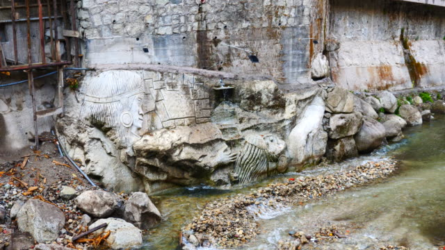 Peru, Aguas Calientes – stone carving with Inca figures at the river bank