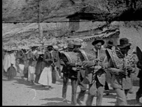 1925 B/W MONTAGE Peruvian fiesta in Andes mountain village. Religious procession though countryside. Indians wear flower headdresses, dance + play musical instruments + flutes / Peru