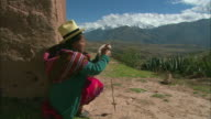 WS Peruvian woman dressed in colorful clothing using drop spindle for wool in mountain landscape / Cuzco Region, Peru