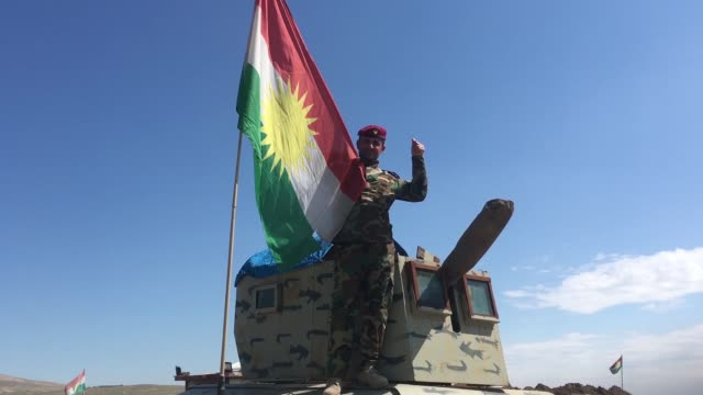 A Peshmerga man with Kurdish flag in a liberated area of Mosul Iraq on March 26 2017 Iraqi Army members take part in the operation to retake Mosul...