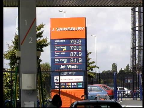 Car into petrol station forecourt CS Display on pump SIDE Man filling car at pumps GV 'BP' petrol station 'J Sainsbury' sign with petrol prices BV...