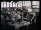 Pharmaceutical industry workers operating machines male cutting large cylinder metal male w/ machine drilling machine producing medicine bottles...