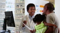 MS PAN Pharmacist Filling Prescription and Talking to Customer at Pharmacy Counter with Child / Richmond, Virginia, USA