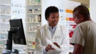 MS PAN Pharmacist Filling Prescription and Talking to Customer at Pharmacy Counter / Richmond, Virginia, USA