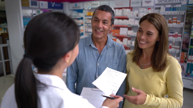 Pharmacist helping a couple at a drugstore with a prescription