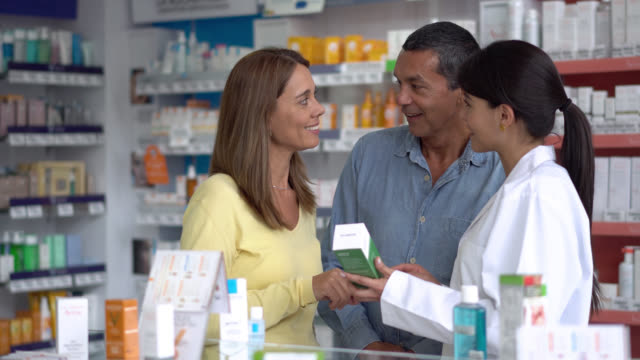 Pharmacist helping a couple with a health product at a drugstore