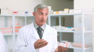 Pharmacist holding a box of pills while talking to a customer