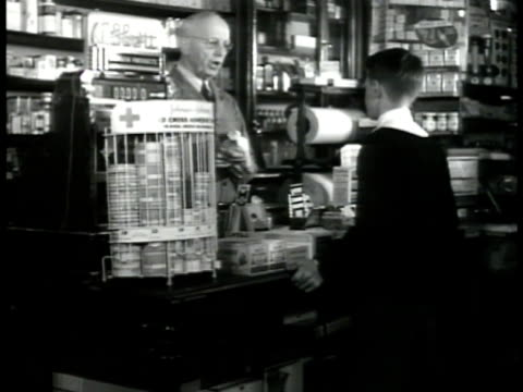 EXETER 'SEWARD' DRUGSTORE DRAMATIZATION MS Pharmacist Mr Seward behind counter talking to boy 'tell your father not to take this all at once...