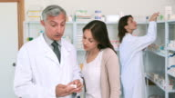 Pharmacist pointing at a flask of pills in front of a customer