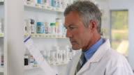 MS PAN Pharmacist Reading Label of Medicine Bottle to Fill Prescription / Richmond, Virginia, USA