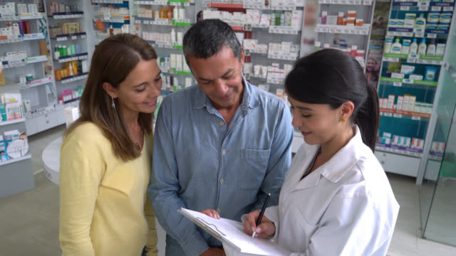 Pharmacist suggesting products to a couple and handing them a paper