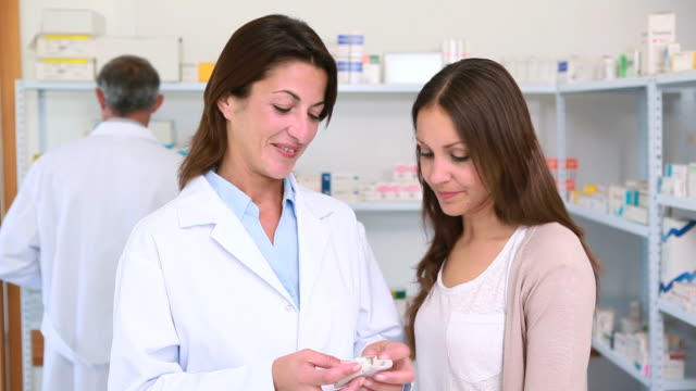 Pharmacist talking to a customer while holding pills