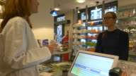 Pharmacist Using Tablet PC While Talking To Woman