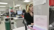 Pharmacists works at computer gets up to get medications from shelves