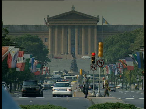 Philadelphia Art Museum traffic pedestrians and flagged lined street in foreground