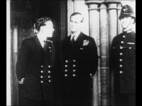 Philip Mountbatten stands arm in arm with Princesses Elizabeth and Margaret / Philip with another naval officer as police officer stands by / CU...