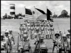 Philippine soldiers marching in parade band playing FG troops in formation BG WS Soldiers marching w/ American Philippine flags MS Sign 'Camp Dau'...