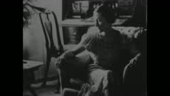 Wallis Simpson in easy chair in home / CU Edward VIII in film circle in middle of screen surrounded by newspaper headlines concerning constitutional...
